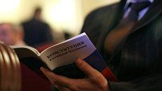 Мужчина с Конституцией РФ в руках на торжественном мероприятии, посвященном Дню Конституции РФ. Архивное фото