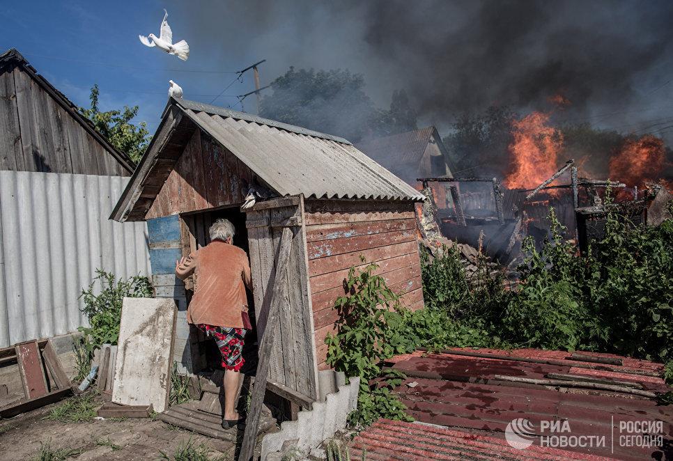 Последствия артобстрела Славянска украинскими военными. Хозяйка горящего дома входит в голубятню
