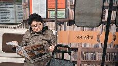 Женщина читет газету в метро. Архивное фото