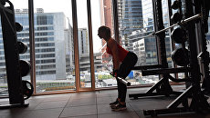 Девушка занимается со штангой в фитнес-клубе. Архивное фото