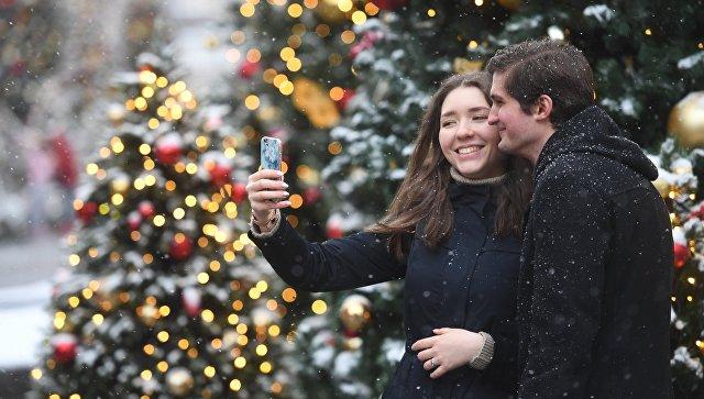 Молодые люди фотографируются во время снегопада в Москве. Архивное фото
