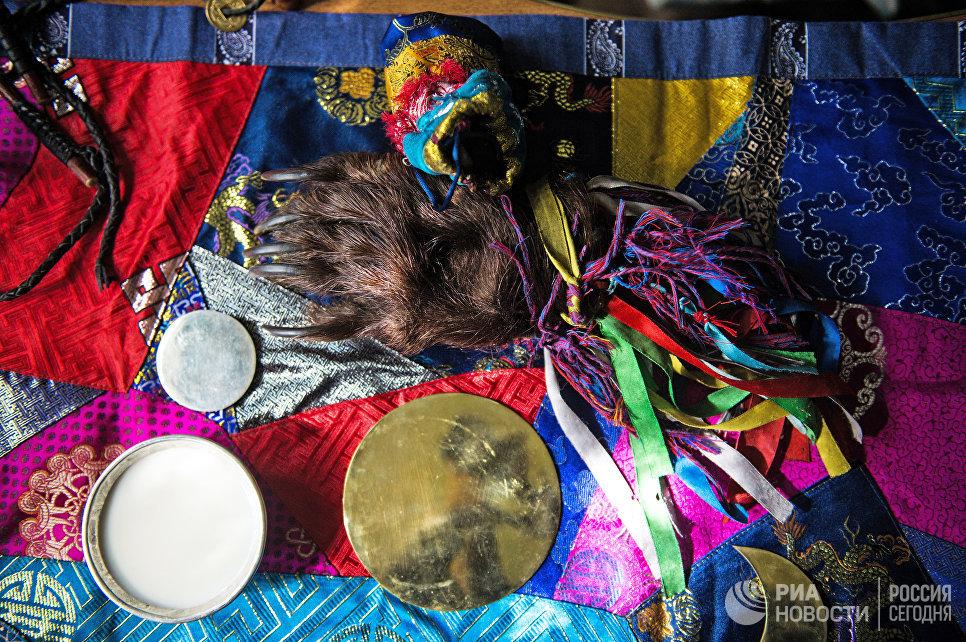 Предметы, используемые шаманом во время проведения обрядов. Одним из главных атрибутов шамана является зеркало – кузунгу. С его помощью шаман проводит камлания, занимается лечением и гаданием.  Медвежья лапа может использоваться, как колотушка для бубна. Тувинские шаманы в своих обрядах часто обращаются к духу медведя.