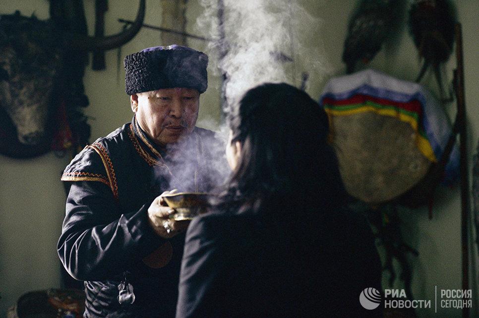 Председатель шаманского общества Адыг-Ээрен (Дух медведя), верховный шаман Республики Тыва Кара-оол Тюлюшевич Допчун-оол проводит обряд с посетителем в своей комнате в доме, который занимает шаманское общество в Кызыле.
