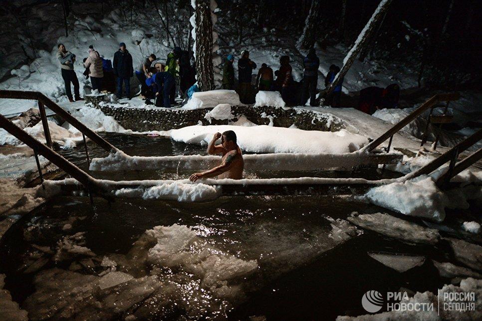 Верующие купаются в купели во время традиционного праздничного купания в Крещенский сочельник на источнике Святой ключ в Искитимском районе Новосибирской области