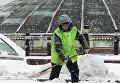 Работник городской коммунальной службы убирает снег на Манежной площади в Москве