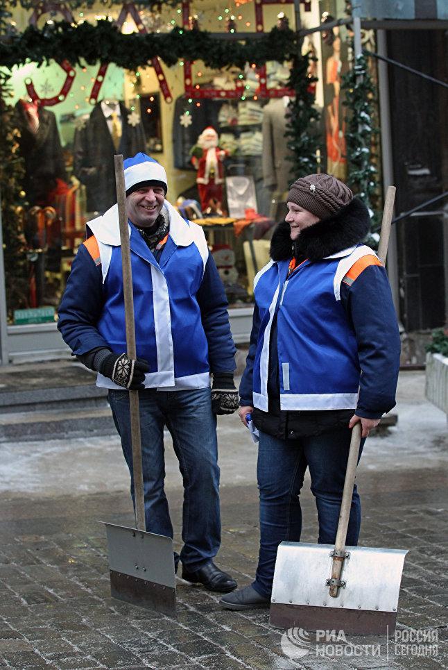 Сотрудники коммунальной службы в новогодних жилетах и шапочках во время проведения акции Утепляем Москву