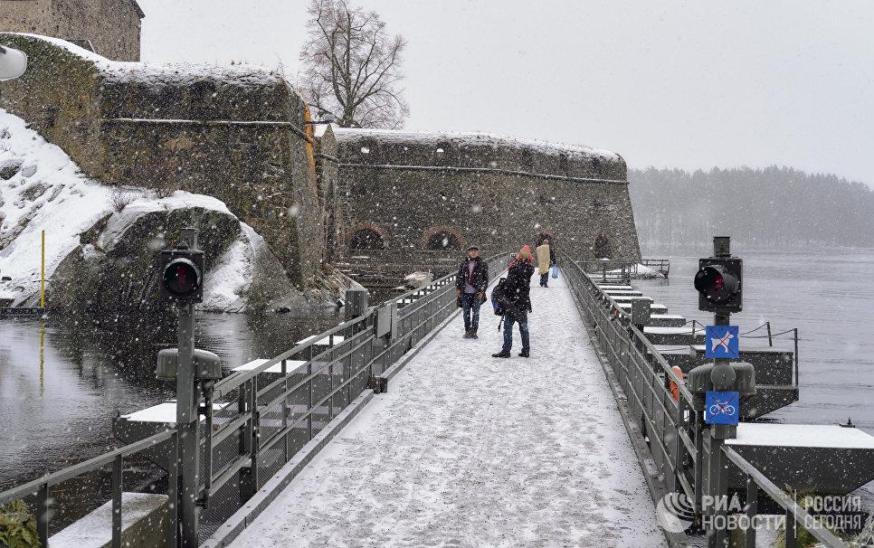 Туристы неподалеку от древнего шведского замка Олавенлинна в городе Савонлинна