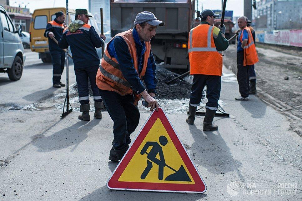 Рабочий устанавливает знак Дорожные работы