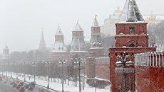Автомобили на Кремлевской набережной в Москве во время снегопада