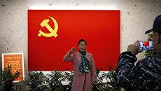Женщина фотографируется у флага Коммунистической партии Китая в Шанхае