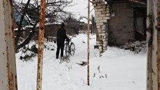Житель поселка Спартак идет между разрушенными домами. Спартак, Донецкая народная республика. Архивное фото