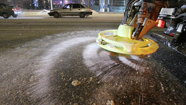Спецтехника служб ЖКХ разбрасывает противогололедный материал во время снегопада на улицах