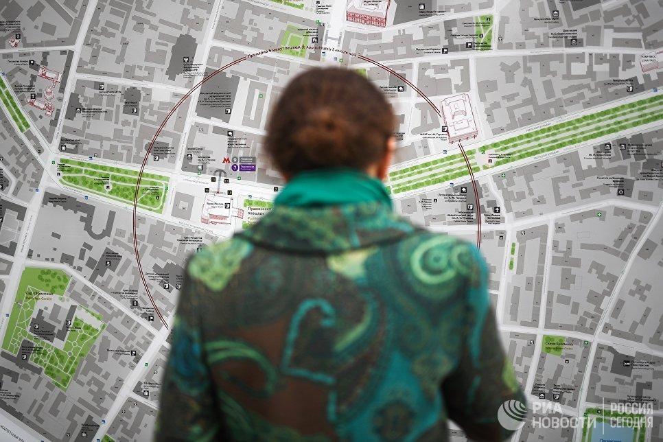 Женщина у информационного табло на Тверской улице в Москве