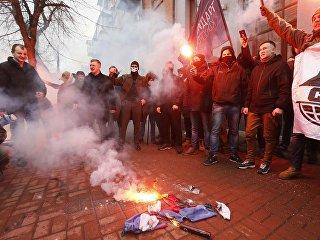 Активисты и сторонники украинских националистических партий сжигают Российский флаг, изьятый из офиса Российского центра науки и культуры в Киеве. 17 февраля 2018