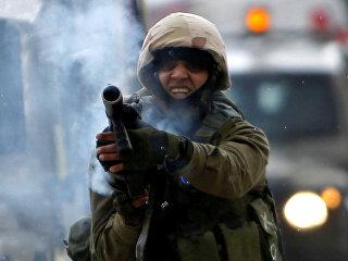 Израильский солдат стреляет в канистру слезоточивого газа во время столкновений в Халхуле. 17 февраля 2018
