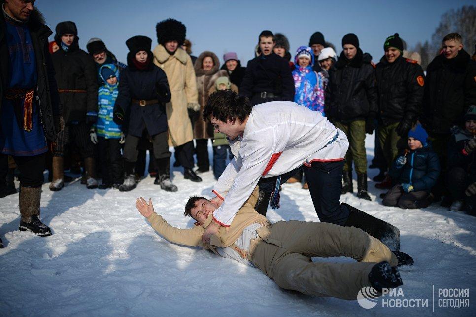 Молодецкие игры во время праздничных гуляний, посвященных проводам Широкой Масленицы в парке наукограда Кольцово в Новосибирской области. 17 февраля 2018