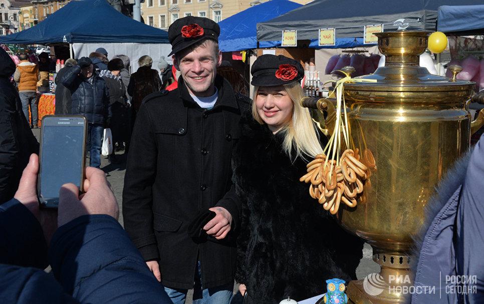 Посетители праздничной ярмарки Широкой Масленицы на центральной площади Владивостока. 17 февраля 2018