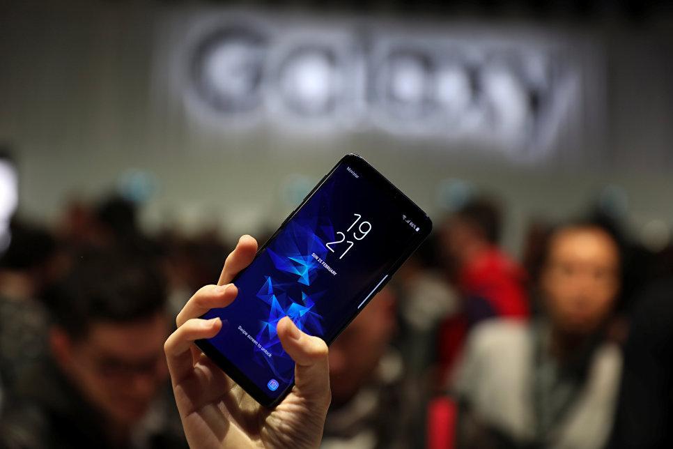 Девушка держит новый смартфон Samsung Galaxy S9 после презентации Mobile World Congress в Барселоне, Испания. 25 февраля 2018 года