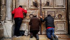 Прихожане молятся у дверей закрытого Храма гроба Господня в Иерусалиме. 25 февраля 2018