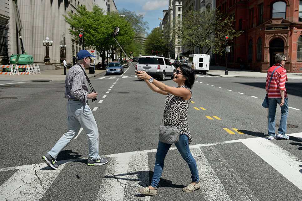 Девушка делает селлфи во время пересечения проезжей части в Вашингтоне, США. 2015 год