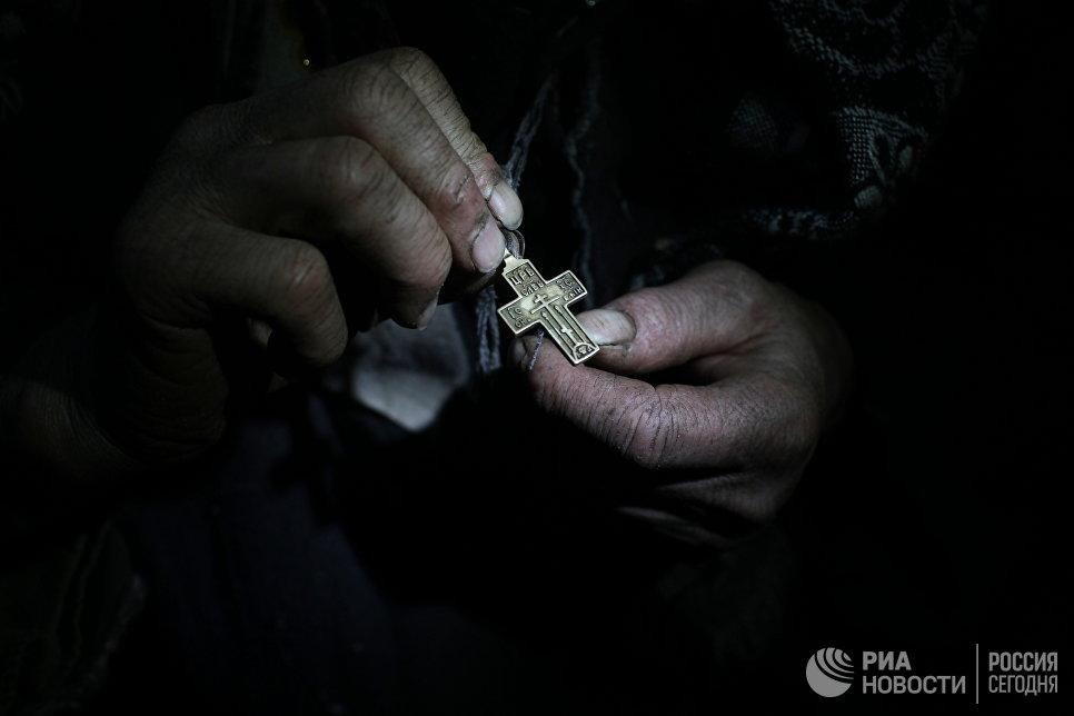 Агафья Лыкова показывает свой нательный крест.