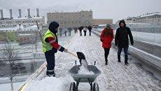 Сотрудник коммунальных служб во время уборки последствий снегопада на Парящем мосту парка Зарядье в Москве