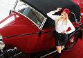 Девушка фотографируется у автомобиля - части специальной экспозиции, посвященной 100-летию пожарной охраны СССР на 27-й выставке старинных автомобилей и антиквариата Олдтаймер-Галерея в московском КВЦ Сокольники