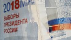 Отражение в окне баннера с информацией о выборах президента России. Архивное фото