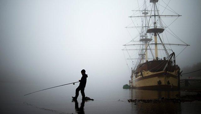 Мальчик ловит рыбу на фоне фрегата Флагман. Архивное фото