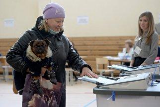 Женщина опускает бюллетень в урну на выборах президента РФ на избирательном участке №1331 в Екатеринбурге. 18 марта 2018