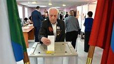 Мужчина опускает бюллетень в урну на выборах президента РФ на избирательном участке в Хабаровске. 18 марта 2018