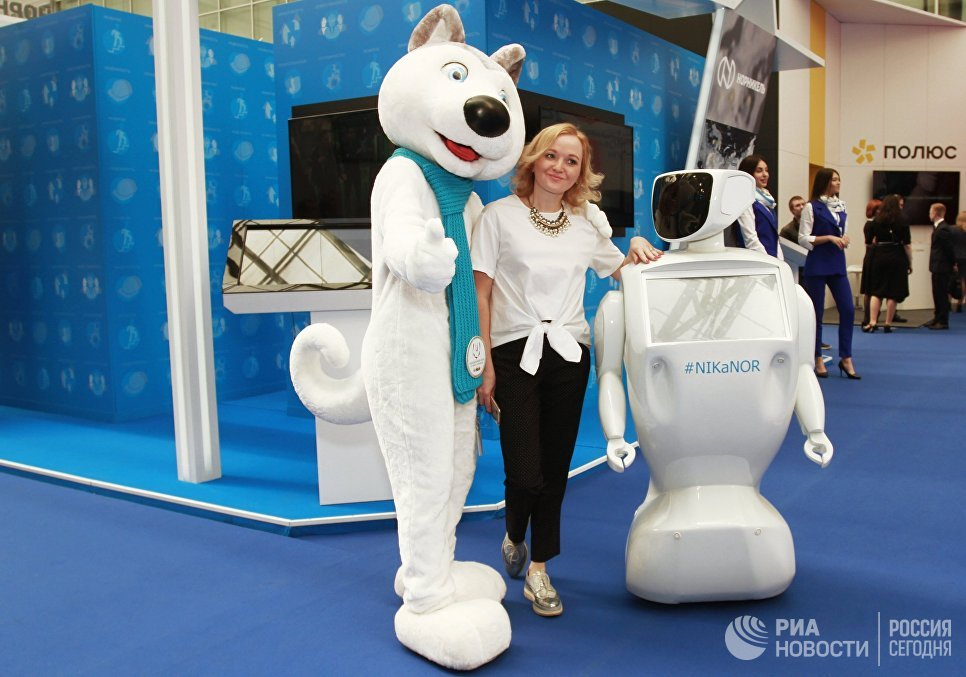Девушка фотографируется с роботом NIKaNOR у стенда компании ГМК Норильский никель на Красноярском экономическом форуме. 12 апреля 2018