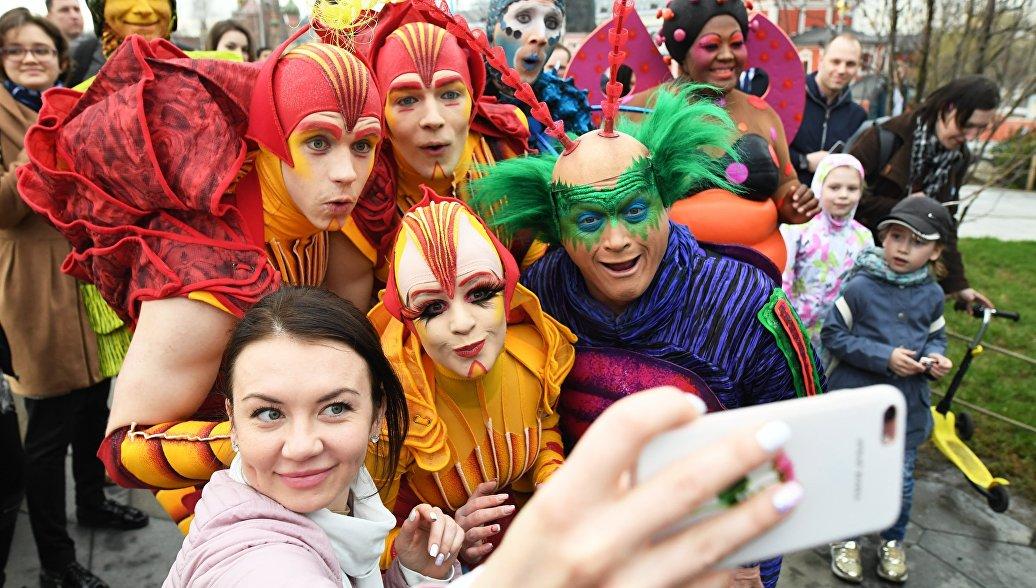 Артисты Cirque du Soleil делают селфи с девушкой на открытии летнего сезона в парке Зарядье в Москве