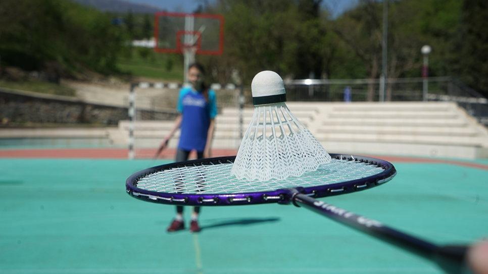 Игра в бадминтон на спортивной площадке детского лагеря Морской