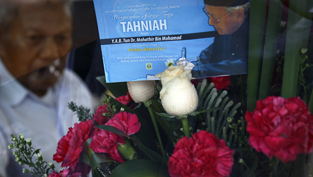 Букет цветов с поздравительной открыткой, на которой изображен новый премьер-министр Малайзии Махатхир Мохамад. 14 мая 2018