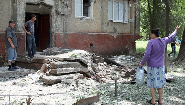 Жители во дворе жилого дома, пострадавшего в результате обстрела, в поселке Горловка Донецкой области. 21 мая 2018