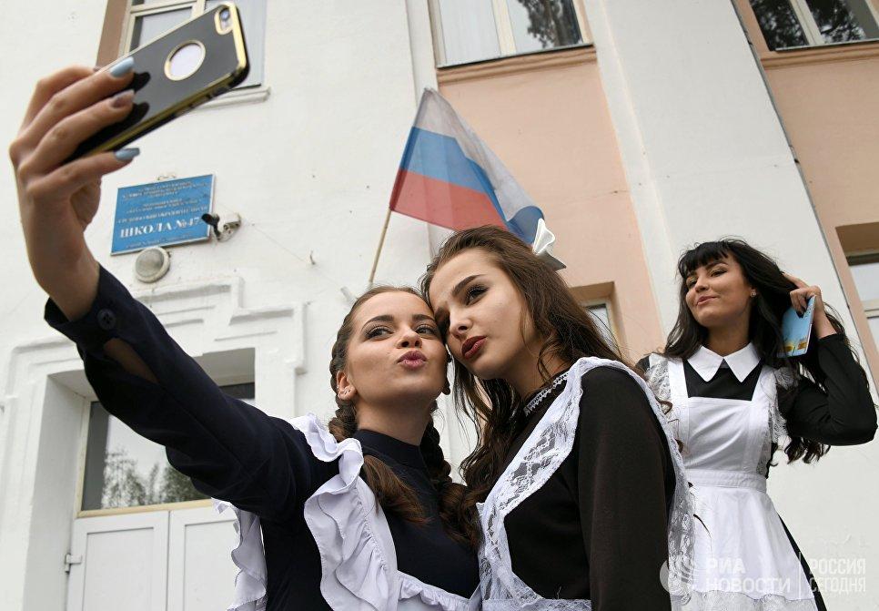Выпускницы делают селфи у входа в школу №47 во время празднования последнего звонка в городе Чите