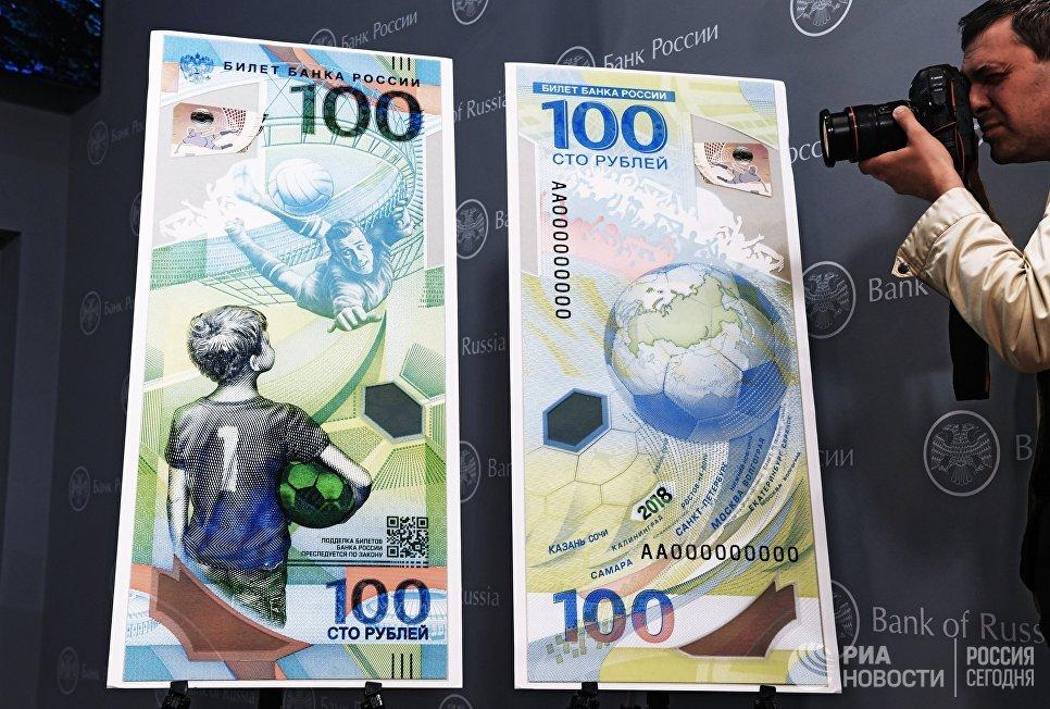 Фотограф фотографирует макет памятной банкноты Банка России, посвященной чемпионату мира по футболу FIFA 2018 года, на пресс-конференции в Москве
