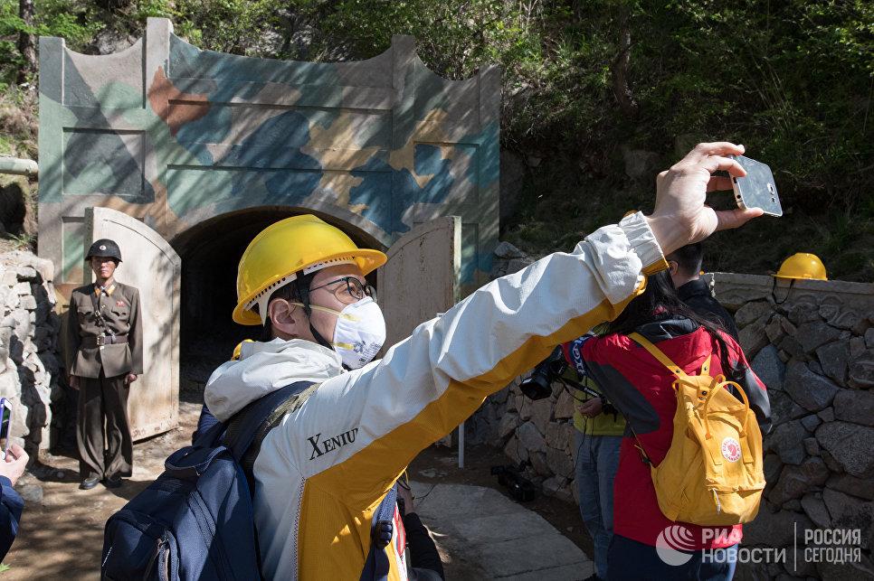 Журналисты из южной Кореи фотографируются у входа в одну из шахт во время закрытия ядерного полигона Пхунгери на севере КНДР