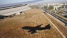 Тень от самолета, прилетающего в международный аэропорт Бен-Гурион в Тель-Авиве, Израиль. Архивное фото