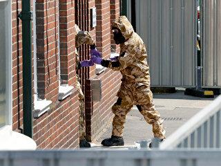Сотрудники британских спецслужб в защитных костюмах у жилого дома в Солсбери в связи с расследованием отравления людей в Эймсбери. Архивное фото