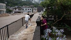 Местные жители во время наводнения в префектуре Хиросима, Япония. Архивное фото