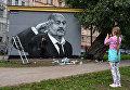 Девушка фотографируется у граффити с главным тренером сборной России по футболу Станиславом Черчесовым на трансформаторной будке в Пушкарском саду в Санкт-Петербурге