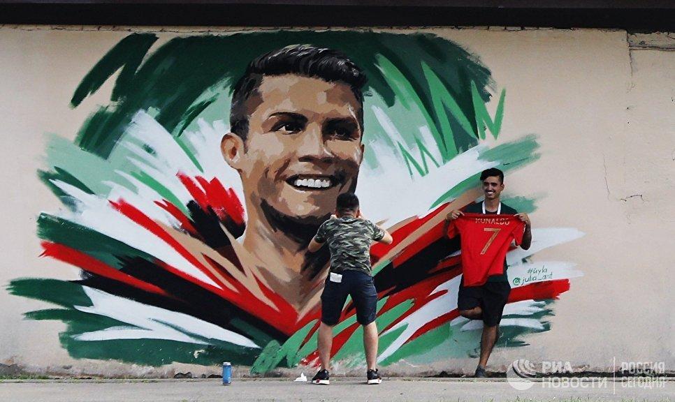 Болельщики рисуют граффити с изображением игрока сборной Португалии Криштиану Роналду перед матчем ЧМ-2018 по футболу между сборными Ирана и Португалии в Саранске