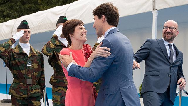 Премьер-министр Канады Джастин Трюдо приветствует гражданскую жену премьер-министра Бельгии Шарля Мишеля. 11 июля 2018