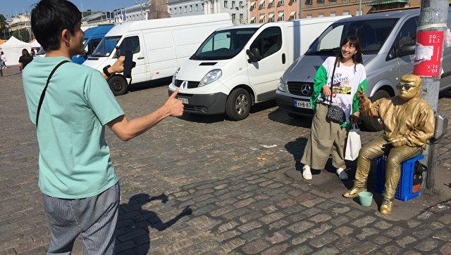 Двойник Трампа и туристы около президентского дворца в Хельсинки. 15 июля 2018