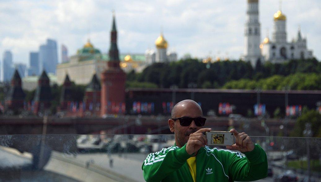Турист фотографируется на фоне Кремля в Москве