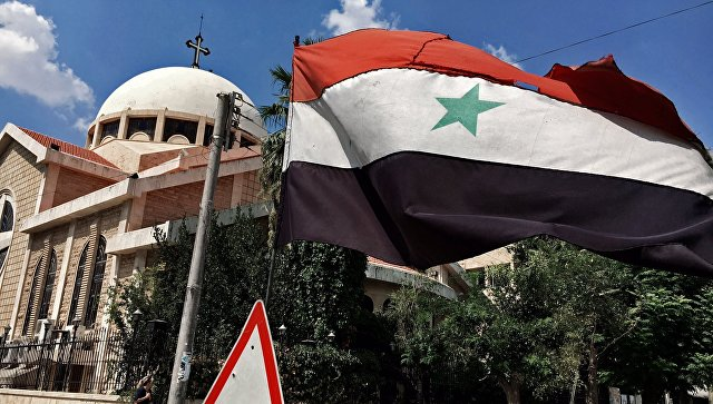 Государственный флаг Сирийской Арабской Республики у православной церкви в старом христианском квартале города Алеппо. Архивное фото
