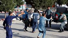 Афганские полицейские несут раненых с места взрыва в Кабуле, Афганистан. 22 июля 2018
