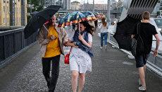 Прохожие на Крымском мосту во время дождя в Москве. Архивное фото